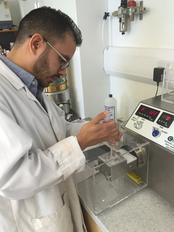 Alejandro Lopez is adding binder to raw materials to create a granulation on the Caleva Multi Lab